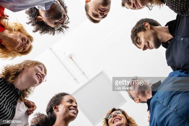 smiling entrepreneurs huddling together in creative office - samen stockfoto's en -beelden
