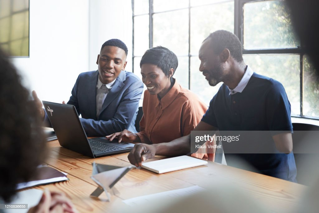 Smiling entrepreneurs in board room during meeting : Stock Photo