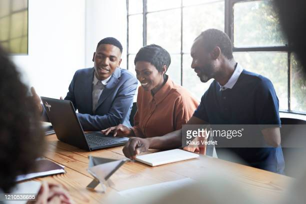 smiling entrepreneurs in board room during meeting - african american ethnicity stock pictures, royalty-free photos & images