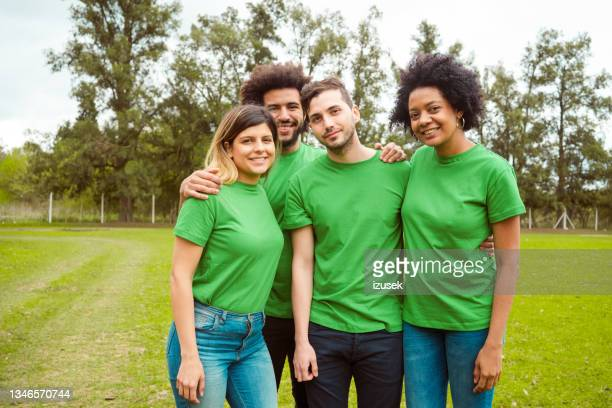 smiling environmentalists in public park - izusek stock pictures, royalty-free photos & images