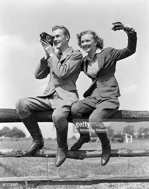 Smiling Equestrian Couple Both Are Wearing Jodhpurs Hacking Jackets & Boots While Sitting On A Rail Fence The Woman Is Waving The Man Is Shooting Movies.