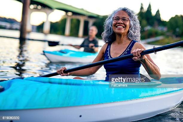 Smiling ethnic elderly woman kayaking with her husband