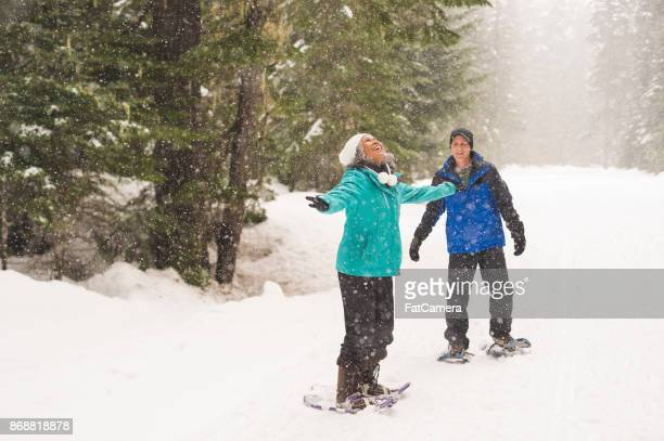 Smiling ethnic senior couple snowshoeing in the forest
