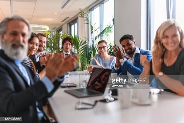 glimlachend executive business team goed nieuws applauden - conferentietafel stockfoto's en -beelden
