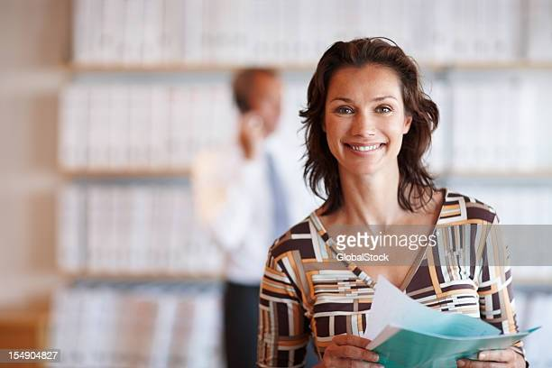 Smiling executive holding folder with colleague in background