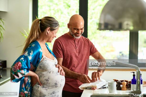 smiling expectant mature couple opening gift in kitchen - human relationship stock pictures, royalty-free photos & images