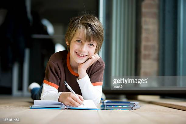 Smiling eye contact from an adolescent boy studying at home