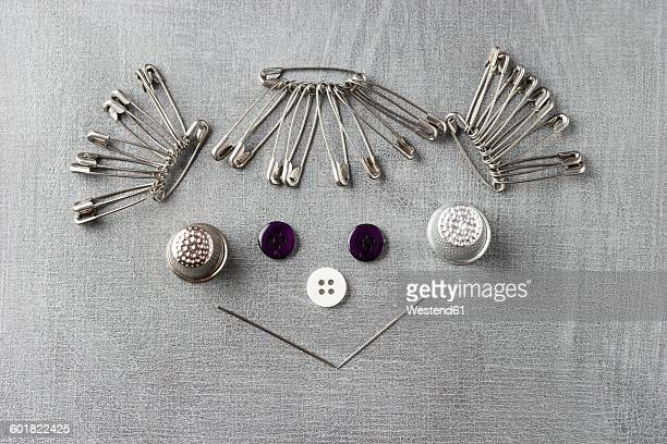 Smiling face of a girl built of sewing items on grey background