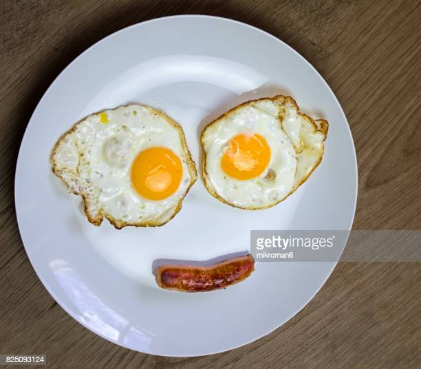 Smiling face on white plate made with fried egg & sausage.