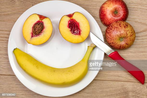 smiling face on white plate made with nectarine  and banana fruits - utility knife stock photos and pictures