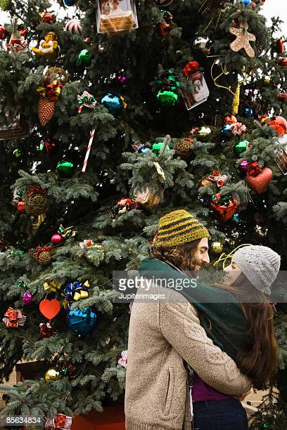 Smiling face to face couple in front of Christmas tree