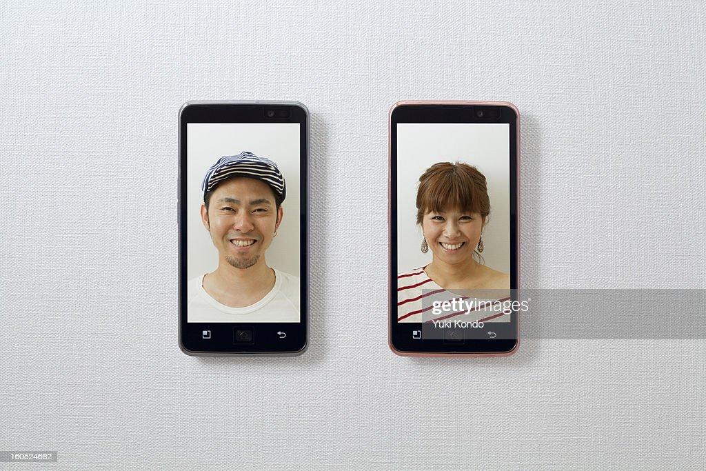 Smiling faces and a smart phones. : Foto de stock