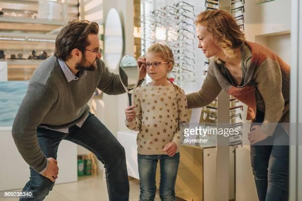 Familie, die Auswahl der geeignetsten Brillen im Optikergeschäft lächelnd.