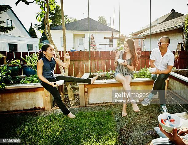Smiling family eating dessert in backyard garden