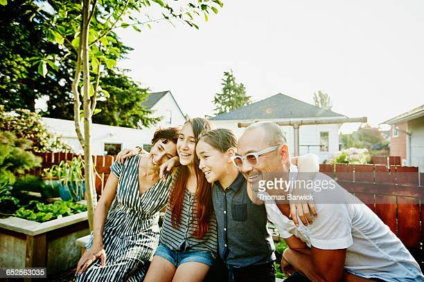 Smiling family embracing in backyard of home