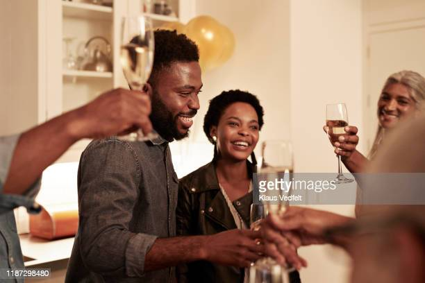 smiling family enjoying drinks at birthday party - anniversary stock pictures, royalty-free photos & images