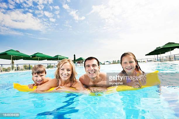 Sonriendo familia disfrutando en la piscina.