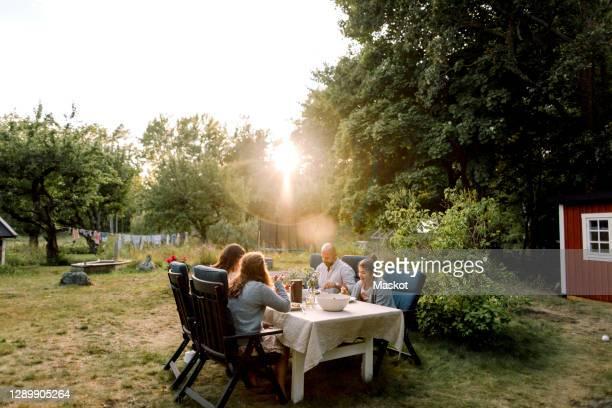 smiling family enjoying while sitting by dining table in yard - landhaus stock-fotos und bilder