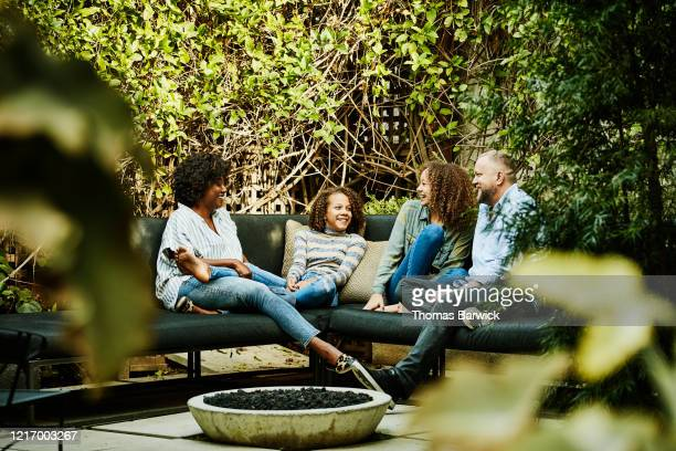 smiling family hanging out by fire pit in backyard - family stock pictures, royalty-free photos & images