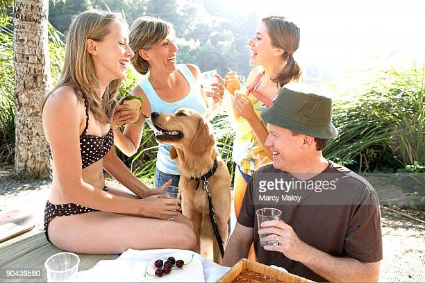 smiling family having a picnic with their dog. - dog eats out girl stock photos and pictures