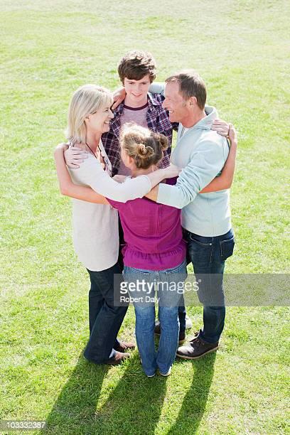 Famille souriant embrassant en cercle sur de l'herbe