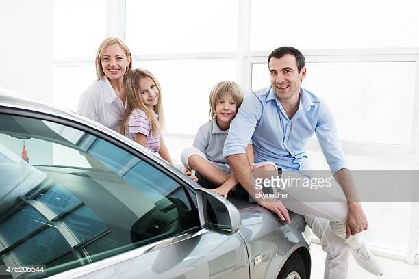 Souriant famille dans une voiture showroom regardant la caméra.