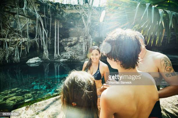 Smiling family in discussion while exploring cenote during vacation