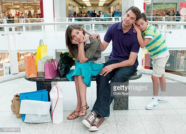 Smiling family in shopping mall relaxing on bench