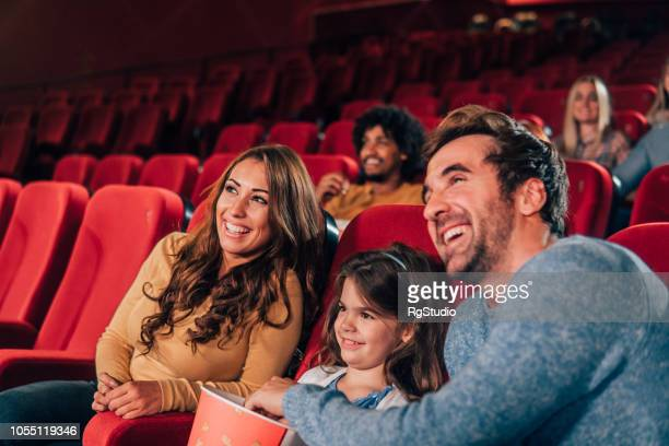 smiling family in the cinema - film industry stock pictures, royalty-free photos & images