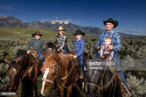 Smiling Family in Western Attire Sitting on Horseback in Beautiful Utah Scenery