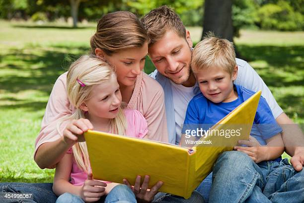 smiling family looking at a photo album - childhood photo album stock photos and pictures