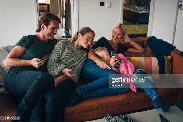 smiling family looking at boy using mobile phone while sitting on sofa at home - four people stock pictures, royalty-free photos & images