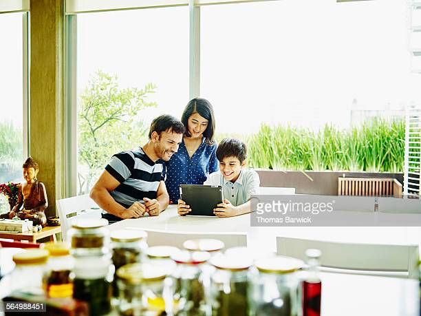 Smiling family looking at digital tablet together