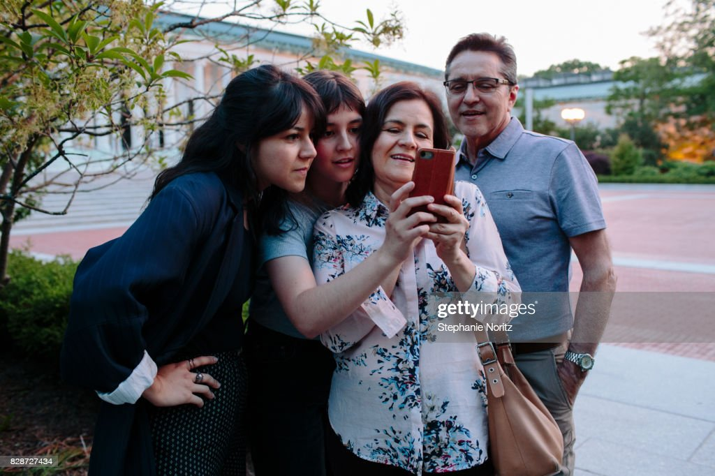 Smiling family looking at smartphone in outdoor setting : Stock Photo
