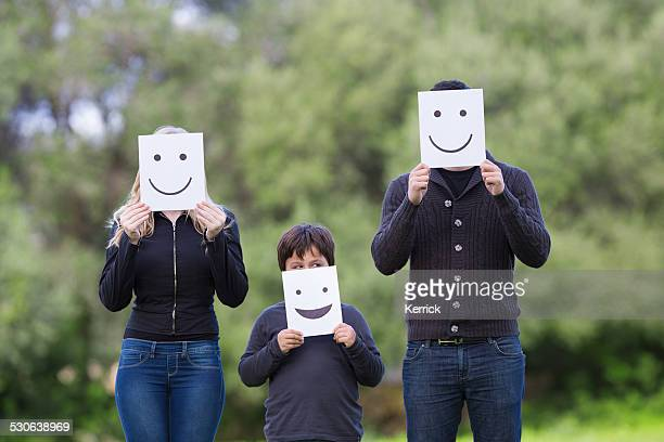smiling family - man, woman and child with smile cardboards