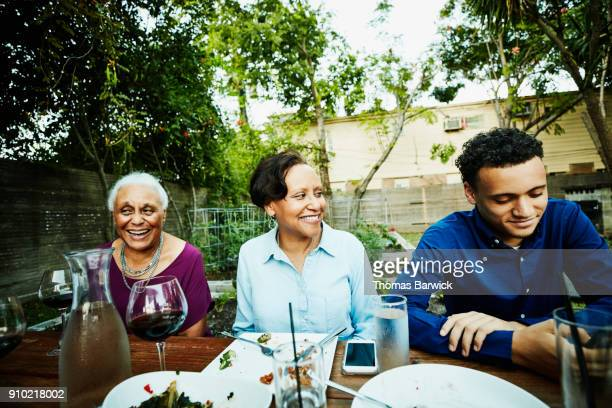 smiling family members in discussion after outdoor dinner party - table after party stock pictures, royalty-free photos & images