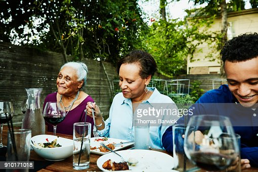 Smiling family members sharing dinner during outdoor celebration meal