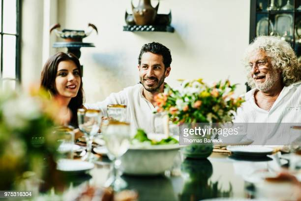 Smiling family members sitting together at dinner table for birthday meal