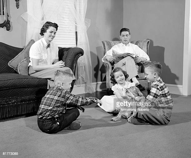 Smiling Family Of 5 Dad Is Sitting In An Arm Chair Mom On The Sofa & The 2 Boys & Girl On The Floor Playing With A Puppy Dad Is Reading A Newspaper.