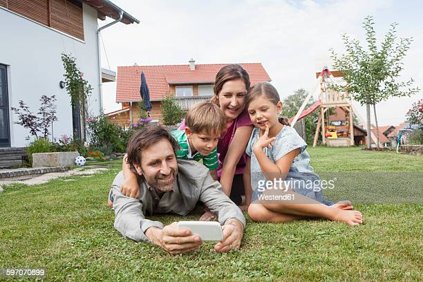 smiling family of four in garden with cell phone - lying on front stock pictures, royalty-free photos & images