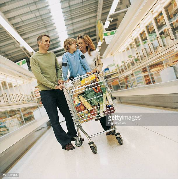 smiling family of three walking down a supermarket aisle with a full shopping trolley - caddie rempli photos et images de collection