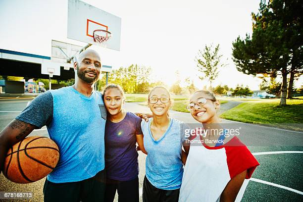 Smiling family on basketball court after game