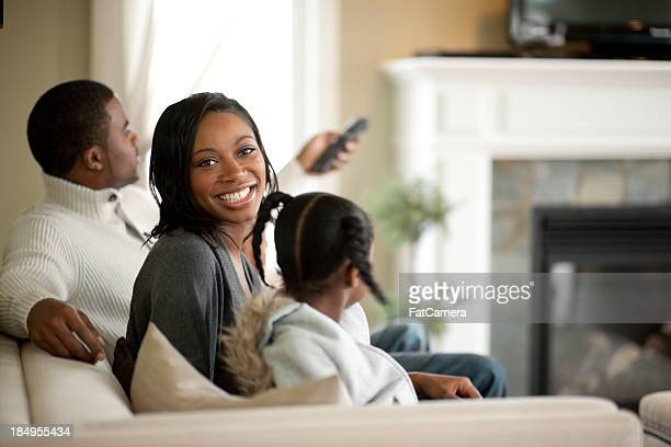 Smiling family on couch watching television