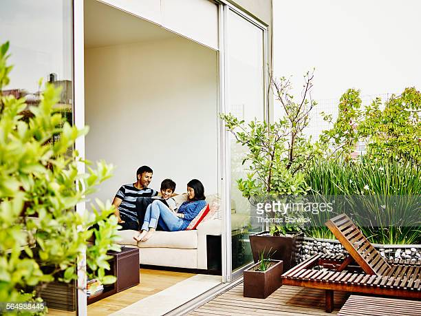 smiling family on sofa looking at digital tablet - patio stock pictures, royalty-free photos & images