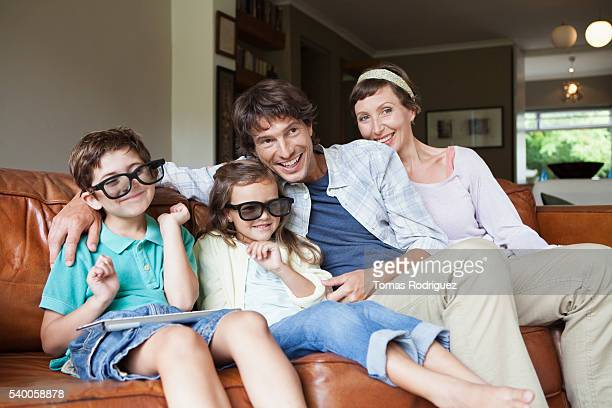 Smiling family on sofa wearing 3D glasses