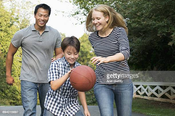 Smiling family playing basketball
