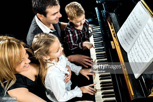 Smiling family playing piano together.
