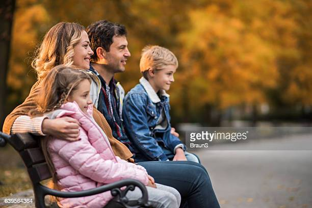 Smiling family relaxing on a bench in the park.