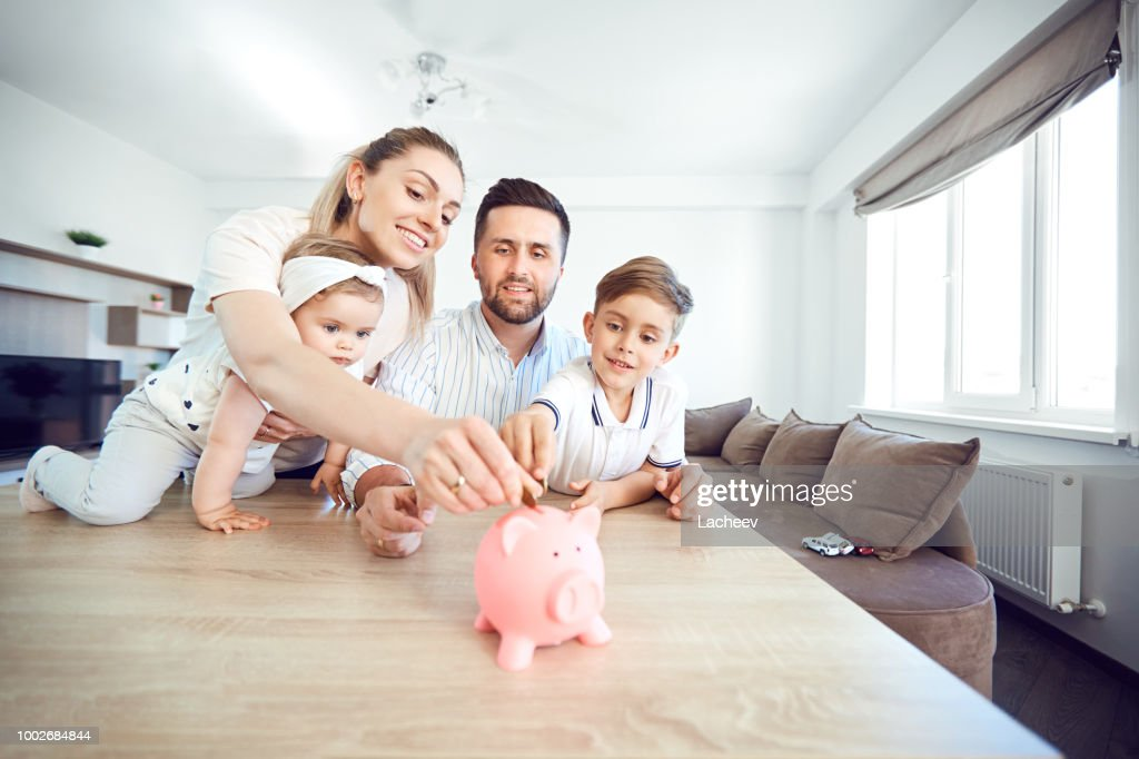 A smiling family saves money with a piggy bank : Stock Photo