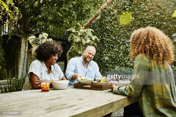 smiling family sharing meal at picnic table in backyard - disruptaging stock pictures, royalty-free photos & images